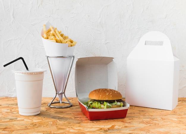 Comida rápida con vaso de eliminación y paquete de comida maqueta en el escritorio de madera