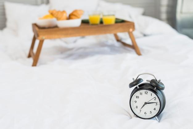 Comida sabrosa en la mesa del desayuno y despertador en la cama.