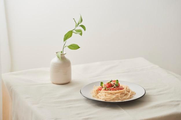 Comida, salsa boloñesa de espaguetis en un plato blanco y un jarrón de plantas sobre una mesa blanca preparada