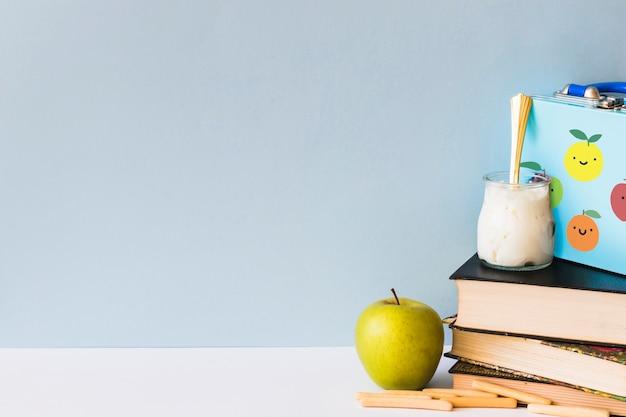 Comida saludable cerca de libros y fiambrera