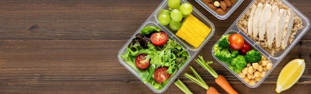 Comida saludable lista para comer en cajas de comida en el fondo de la bandera de madera