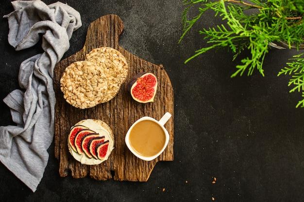 Comida saludable, sándwich, pan crujiente, higos, café, desayuno o merienda, queso crema, mantequilla, menú de yogurt. comida copyspace vista superior