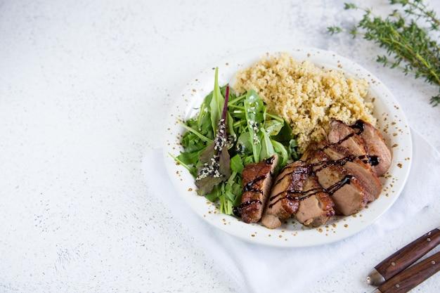 Comida saludable. servir cuscús con ensalada y pechugas de pato asadas