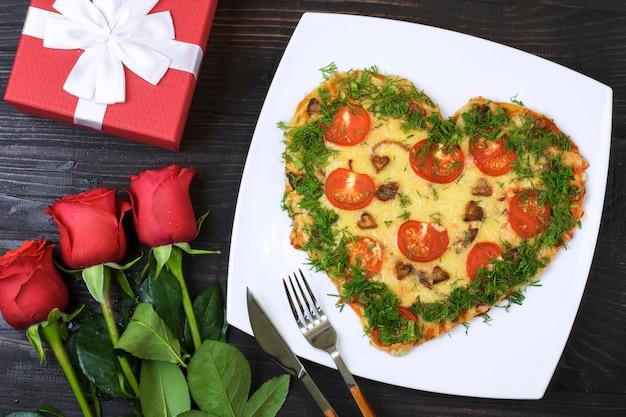 Comida de san valentín. pizza en forma de corazón junto a un regalo y rosas rojas, sobre un fondo de madera oscura.
