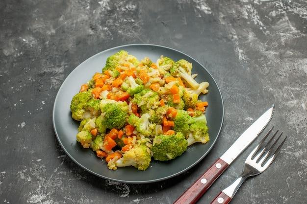 Comida sana con brocoli y zanahorias en una placa negra con tenedor y cuchillo sobre mesa gris