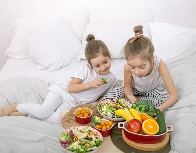 Comida sana en casa. felices dos niños lindos comiendo frutas y verduras en el dormitorio de la cama. alimentos saludables para niños y adolescentes.