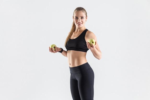 Comida sana, comida fresca, concepto de dieta. mujer atlética sosteniendo manzana verde orgánica, dentuda sonriendo y mirando a la cámara