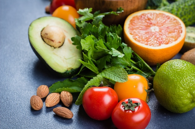Comida sana concepto limpio. frutas crudas, verduras, nueces, cereales en el fondo de la tabla de piedra concreta
