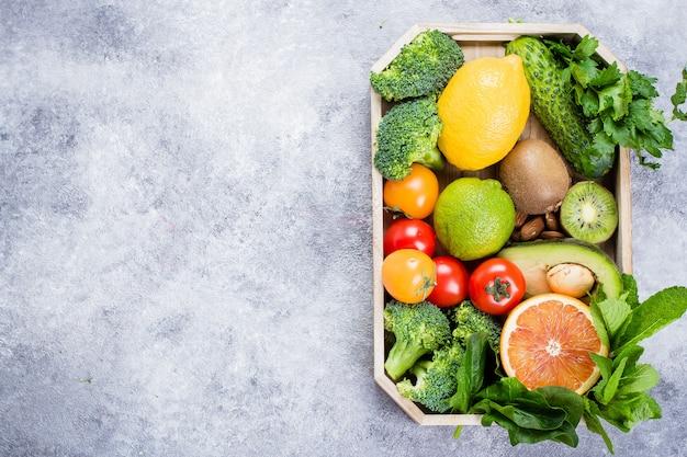 Comida sana concepto limpio. frutas, vegetales, nueces, cereales en bandeja de madera.