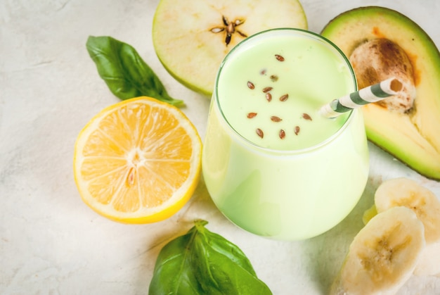 Comida sana. desayuno dietético o merienda. batidos verdes de yogur, aguacate, plátano, manzana, espinacas y limón. sobre mesa de piedra de hormigón blanco, con ingredientes. copia espacio