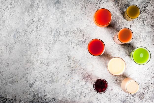 Comida sana, diferentes jugos de frutas y verduras batido en copas vista superior copyspace