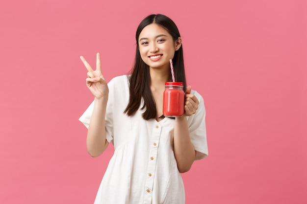 Comida sana, emociones y concepto de estilo de vida de verano. feliz chica asiática guapa con vestido blanco, mostrando el signo de la paz kawaii y bebiendo batido de vidrio y paja.