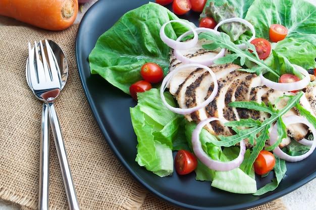 Comida sana, ensalada asada a la parrilla de la pimienta negra del pollo en la tabla concreta. concepto de dieta o cocina