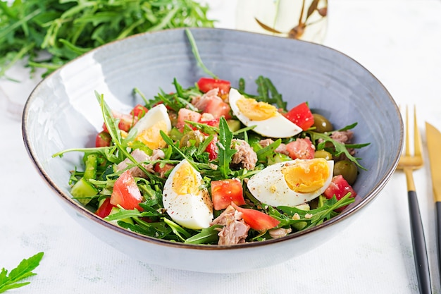 Comida sana. ensalada de atún con huevos, pepino, tomate, aceitunas y rúcula. cocina francés.