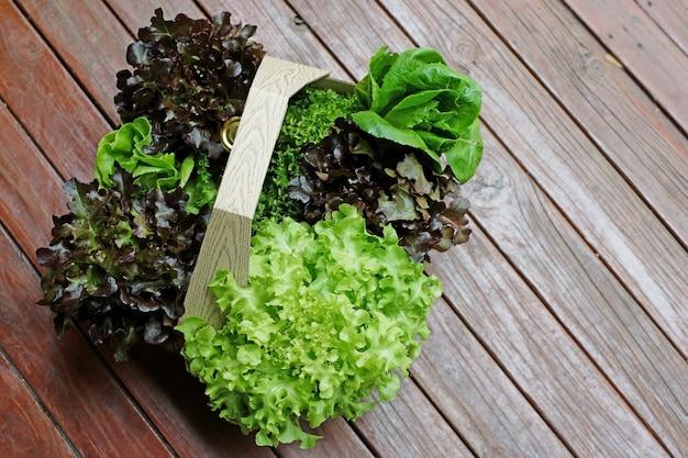 Comida sana, ensalada de verduras en la canasta sobre un piso de madera