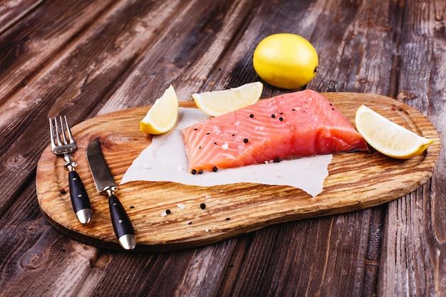 Comida sana y fresca. salmón crudo servido con limones y cuchillos en tabla de madera