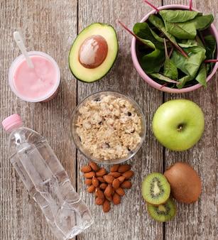 Comida sana, fruta, yogur, cereal y botella de agua.
