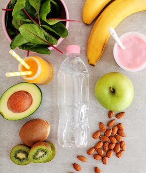 Comida sana, frutas y botella de agua.