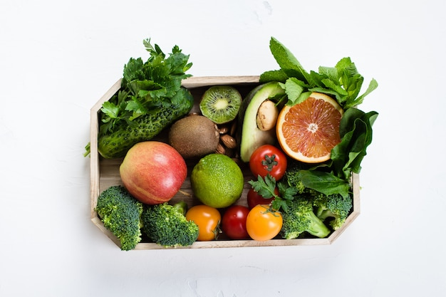 Comida sana limpia. frutas crudas, verduras, nueces, cereales en bandeja de madera en fondo concreto.