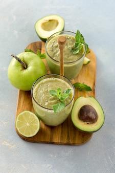 Comida sana y limpia, taza de vidrio con batido de salud verde de manzana, espinaca, lima y aguacate sobre una mesa