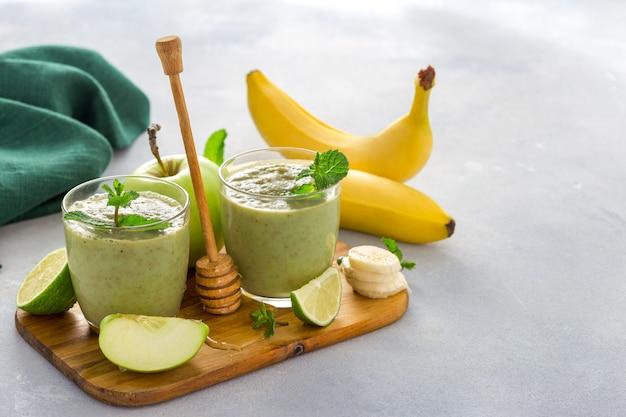 Comida sana y limpia, taza de vidrio con batido de salud verde de manzana, espinaca, limón y miel sobre una mesa