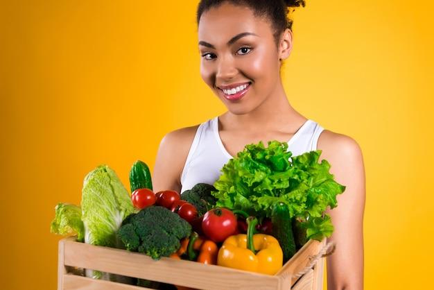 Comida sana la niña en manos de verduras.