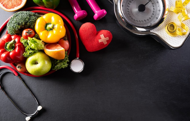 Comida sana en plato con estetoscopio, báscula y corazón rojo