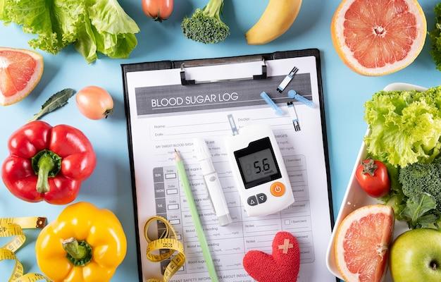 Comida sana en plato con estetoscopio y corazón rojo para el control de la diabetes