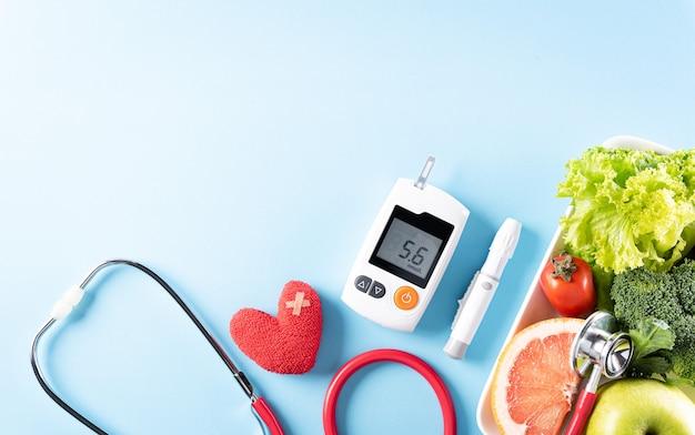 Comida sana en plato con estetoscopio y corazón rojo para la dieta del colesterol y el control de la diabetes