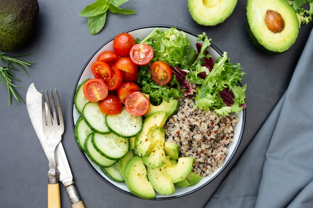 Comida sana. tazón de budha con quinua, aguacate, pepino, ensalada, tomate, aceite de oliva.