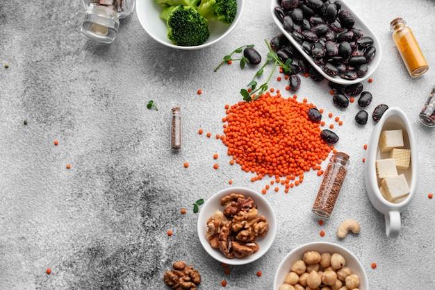 Comida sana del vegano en un fondo concreto con el espacio de la copia. frutos secos, alubias, verduras y semillas.
