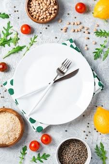 Comida sana. verduras, limón y garbanzos alrededor del plato blanco vacío en una mesa de concreto, vista superior. concepto de comida vegetariana y vegana endecha plana.