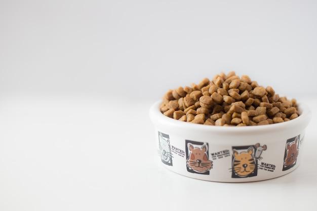 Comida seca para gatos o perros en un tazón blanco sobre un fondo blanco.