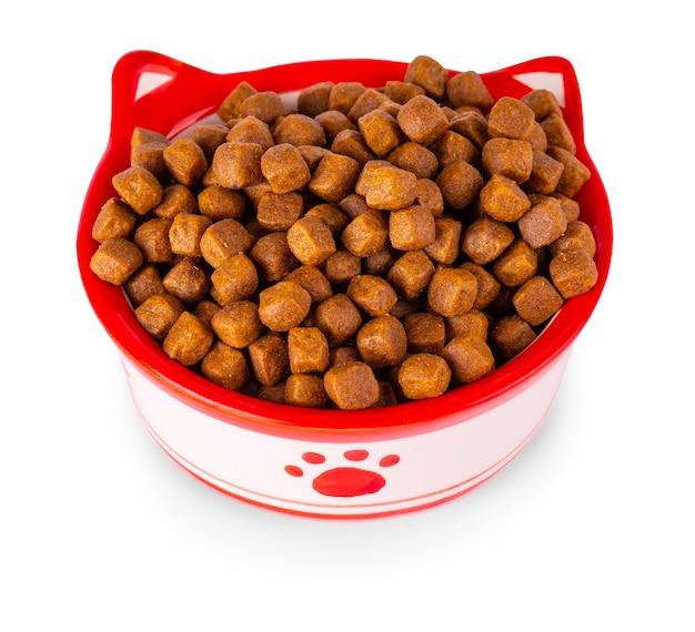 La comida seca para gatos en un recipiente, aislado sobre fondo blanco.