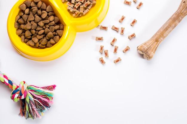 Comida seca para mascotas en un tazón y juguetes para perros en la vista superior de fondo blanco
