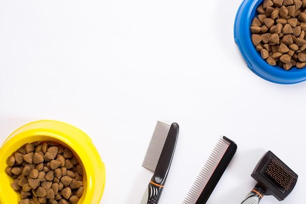 Comida seca para mascotas en un tazón peines y cepillos para perros en la vista superior de fondo blanco