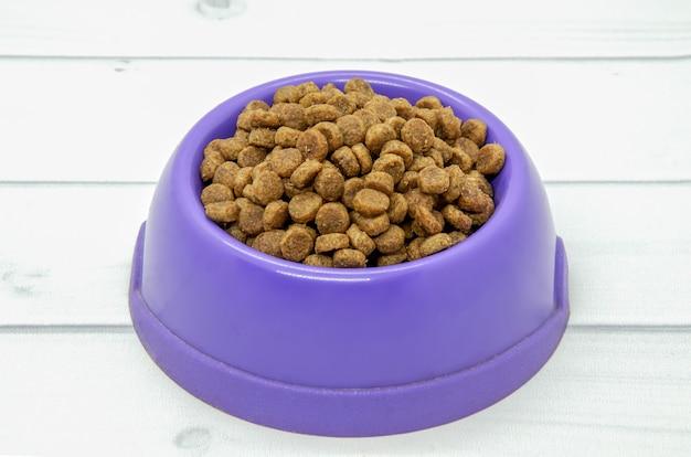 Comida seca para perros en un recipiente de plástico púrpura sobre un piso de madera clara.