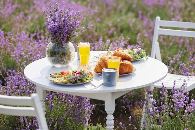 Comida servida en mesa en campo lavanda