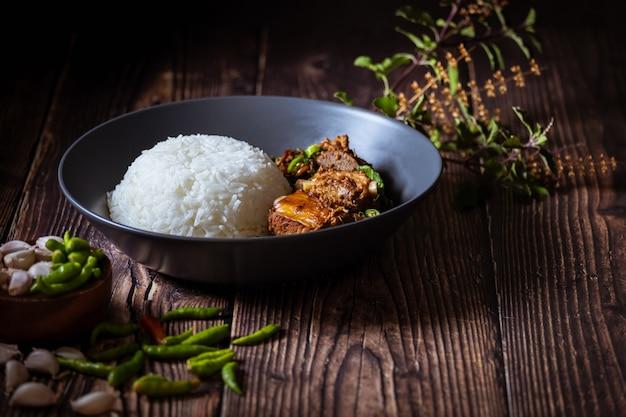 Comida tailandesa, arroz cubierto con albahaca frita y hueso de cerdo.