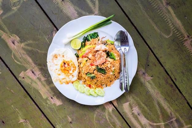 Comida tailandesa, arroz frito, mariscos, camarones, calamares y huevo frito sobre fondo de madera