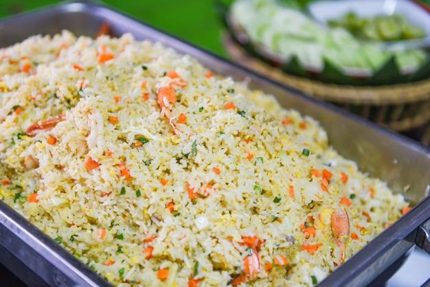 Comida tailandesa buffet arroz frito camarones zanahoria y verduras en la bandeja en la mesa del comedor /