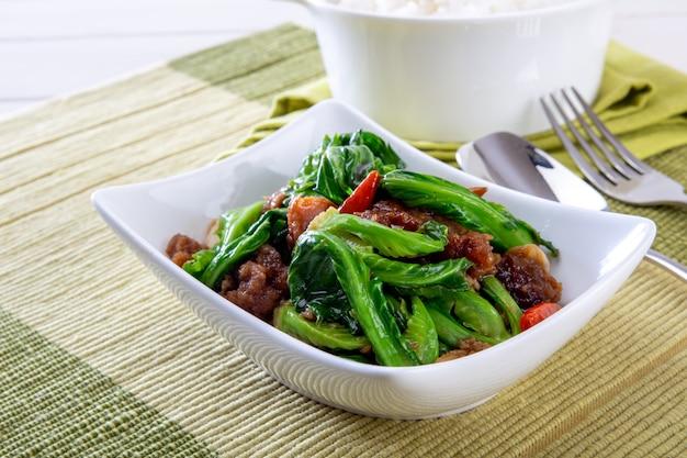 Comida tailandesa o cocina tailandesa, revuelva la col rizada con cerdo curruscante con arroz.