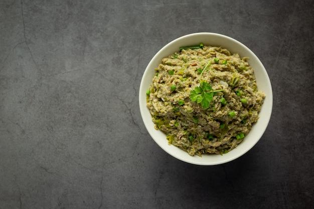 Comida tailandesa; pasta de ají de caballa en un tazón blanco en lugar oscuro sobre el piso