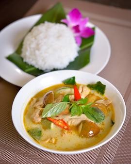 Comida tailandesa pollo al curry verde con arroz en madera