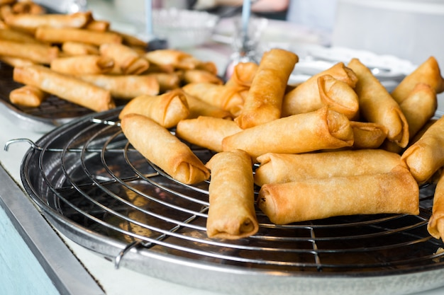 Comida tailandesa, rollos de primavera fritos en la placa negra del hierro en fondo de piedra gris de la pizarra.