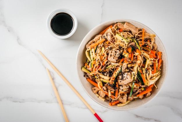 Comida tradicional asiática. almuerzo salteado con fideos de arroz, calabacín, zanahorias, bambú, champiñones, carne