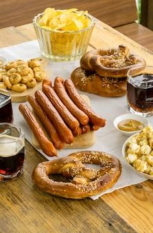 Comida tradicional del festival de octubre. salchichas, aperitivos y cerveza en una mesa de madera
