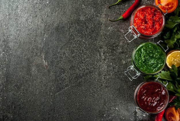 Comida tradicional india, conjunto de tres chutney para chaat y sev puri: dulce de tamarindo de dátiles, cilantro, menta y ajo rojo, en la superficie de piedra oscura, copie la vista superior del espacio