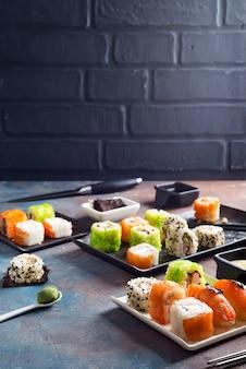 Comida tradicional japonesa sushi, rollos, palillos, salsa de soja sobre piedra de color