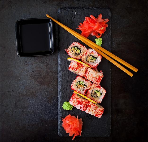 Comida tradicional japonesa - sushi, rollos y salsa sobre un fondo negro. vista superior